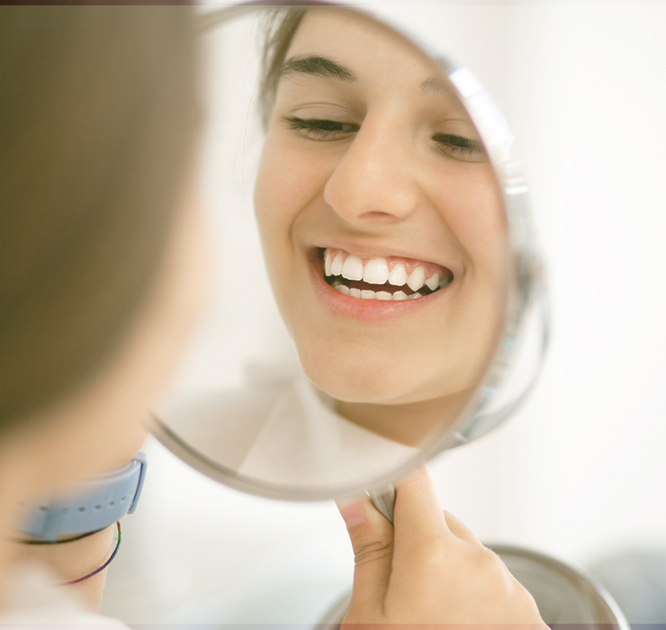 A woman looking in the mirror and smiling after her cosmetic treatment.