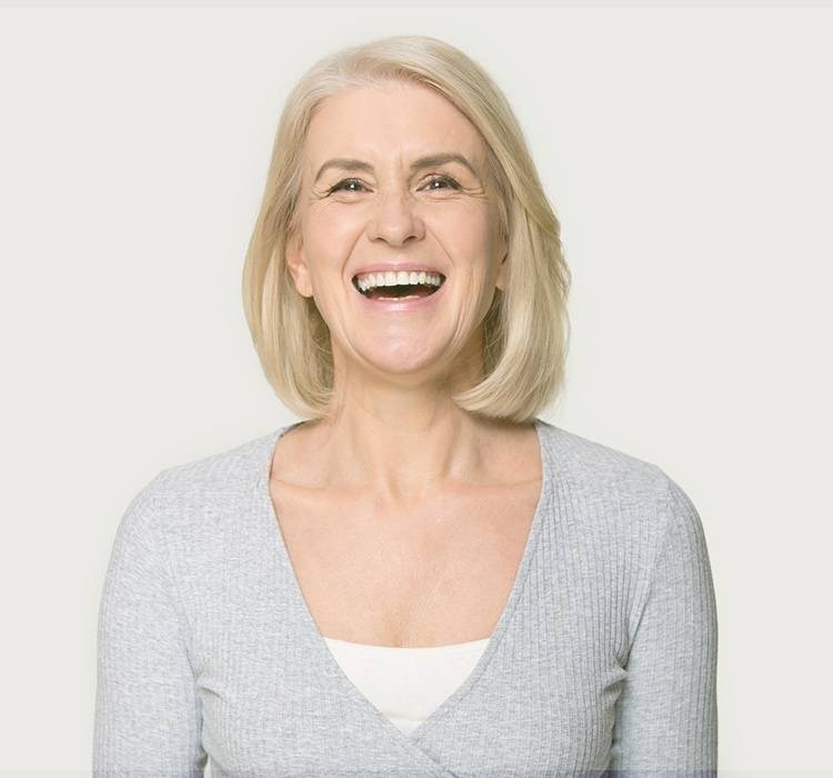 A woman smiling after her restorative treatment.