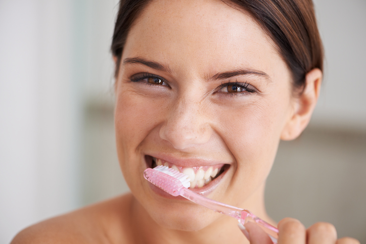 A healthy smiling woman engaging in Dental Hygiene by brushing her teeth in East Wenatchee, WA